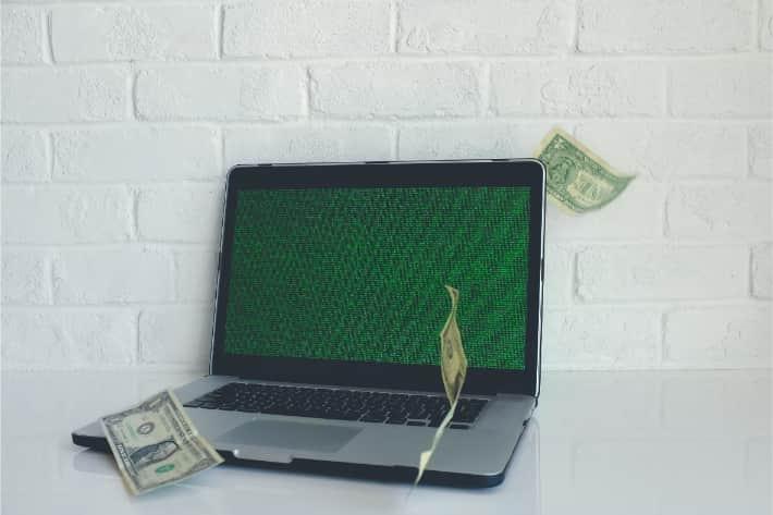 Взломанный компьютер с падающей американской долларовой купюрой