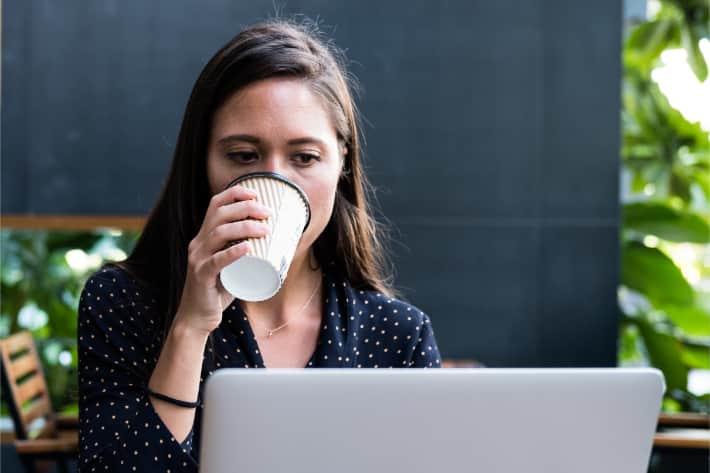 Женщина просматривает ноутбук и пьет кофе